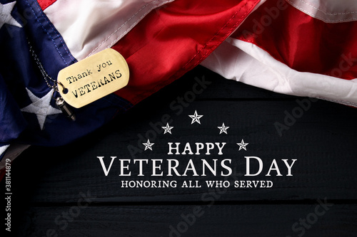 Closeup of a dog tag with the text thank you veterans engraved in it, next to a flag of the United States, on black wooden background.