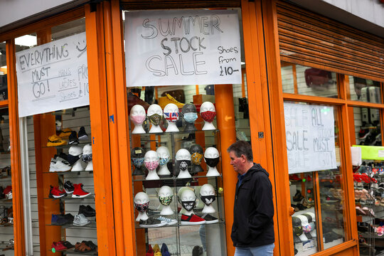 Masks sit on display as a pedestrian walks past in Brixton, London