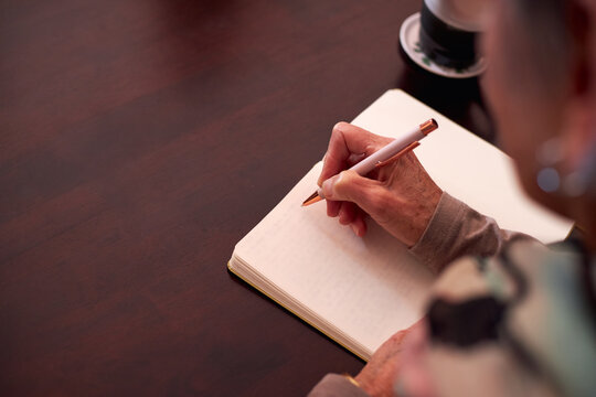 Close Up Of Senior Woman At Home Sitting At Table And Writing In Notebook Or Journal