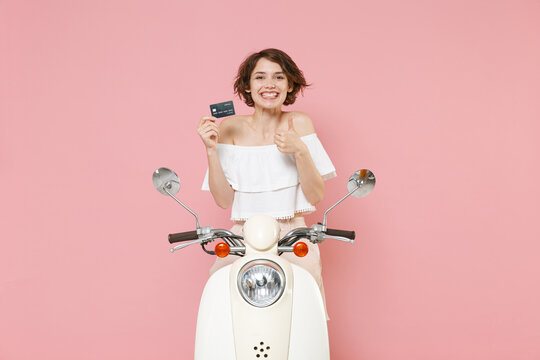 Smiling young brunette woman 20s wearing white summer clothes posing hold credit bank card showing thumb up looking camera sit driving moped isolated on pastel pink colour background, studio portrait.
