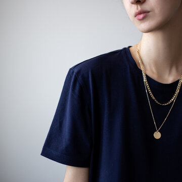 Closeup photo of yping woman wearing dark t-shirt and golden necklace