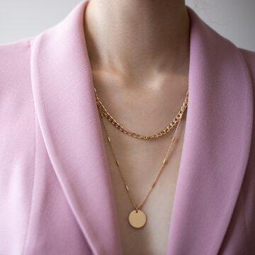 Closeup photo of young woman wearing pink jacket and golden necklace