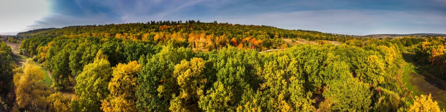 Panoramic aerial view over colorful green and orange autumn forest in countryside in Samara region, Russia