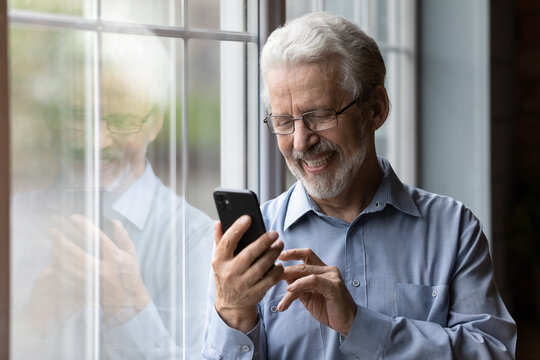 Happy senior Caucasian man in glasses look at cellphone screen browse wireless internet. Smiling modern mature 70s grandfather text or message on smartphone. Elderly use cell technologies at home.