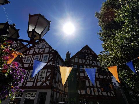 Mit Wimpeln geschmückte Fachwerk-Straße im Schatten der sommerlichen Abendsonne in Dillenburg