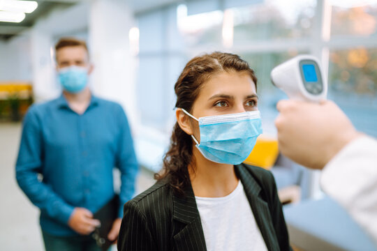 Disease control experts use an Infrared thermometer equipment to check the temperature on the forehead before entering at office. Сhecking the temperature of office workers. Covid-19.