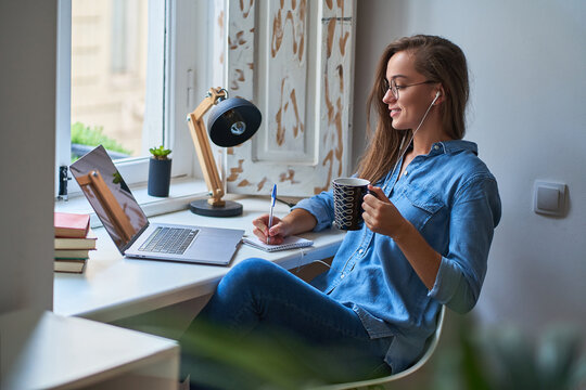 Casual young smiling smart woman student in headphones satisfied with learning foreign language. Female making notes at notebook during watching webinar video courses. Online education