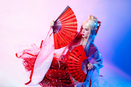 a woman in a geisha costume with fans sits on a white background