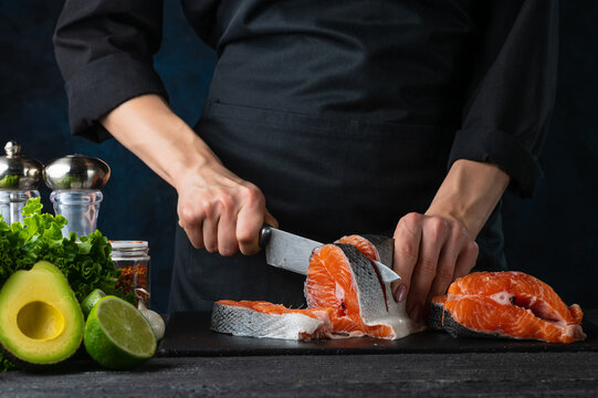 Close-up of chef cuts with knife the salmon at the professional kitchen. Dark background for background. Backstage of preparing restaurant dinner. Food concept.