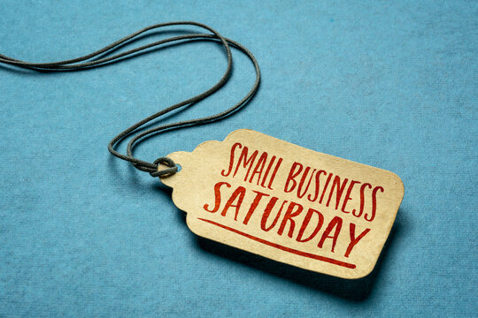 Small Business Saturday sign - a paper price tag with a twine against blue paper background, local holiday shopping concept