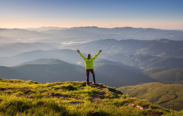 Sporty man standing on the mountain peak with raised up arms against mountain valley in fog at...