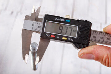 Measuring the thread diameter with an electronic caliper. Measuring accessories in a home workshop.