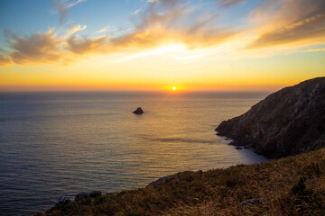 sunset in the sea of ​​finisterre, orange yellow and blue sky