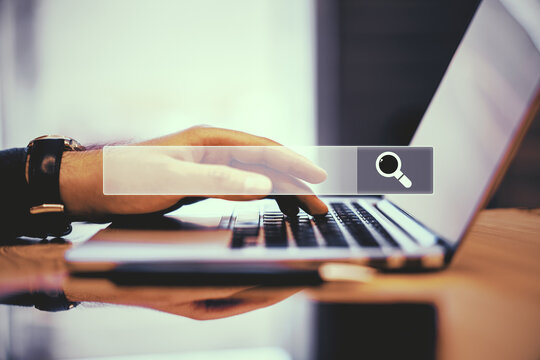 Hand working on laptop with search bar