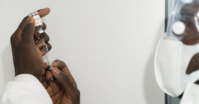 coronavirus covid-19 vaccine in bottle in hands of african american doctor