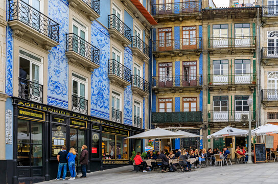 Porto, Portugal - May 30, 2018: Facades of restaurants and bars on a city square in traditional houses decorated with ornate Portuguese azulejo tiles