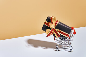 Shopping cart with gift box on beige gray background. Gifts wrapped in kraft black paper with ribbon and bow. Holiday Shopping concept