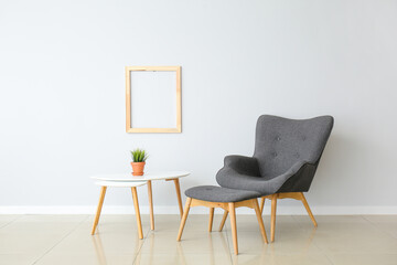 Wall Mural - Stylish armchair and ottoman with table near light wall in room