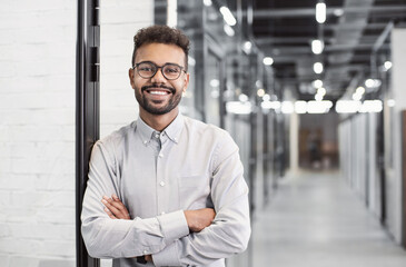 Obraz Handsome young businessman with folded arms in the office, Cheerful self confident men with crossed hands portrait, Business success concept - fototapety do salonu