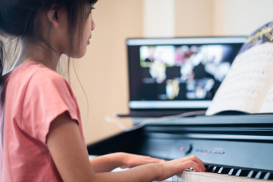 Homeschool Asian young girl learning piano from music online class.