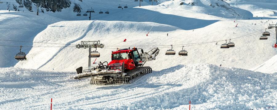 Red modern snowcat ratrack with snowplow snow grooming machine preparing ski slope piste hillalpine skiing winter resort Ischgl in Austria. Heavy machinery mountain equipment track vehicle. panoramic