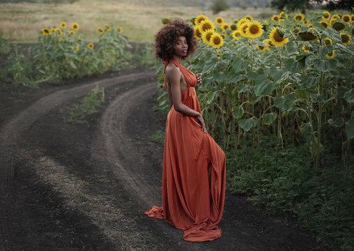 Young black woman in a long orange dress walks in the sunflower field.