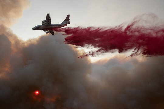 An airplane drops red fire retardant on the Glass Fire in Deer Park, California