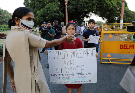Licypriya Kangujam carrying a placard is stopped by a policewoman during a protest demanding to pass a climate change law outside the parliament in New Delhi