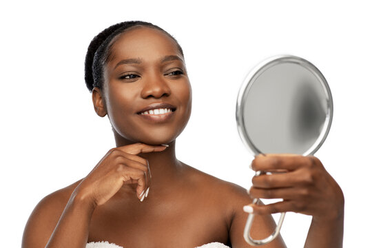 beauty and people concept - portrait of happy smiling young african american woman with bare shoulders looking to mirror over white background