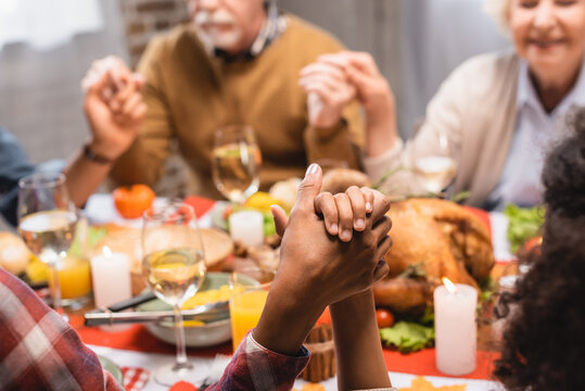 cropped view of multicultural family holding hands while praying during thanksgiving dinner