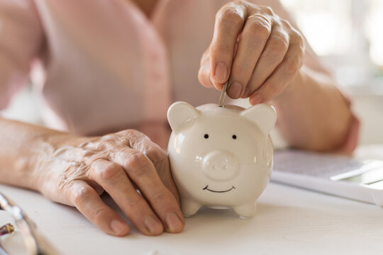 Old women's hands put money coins in a piggy Bank, the concept of retirement, savings, savings, old age.