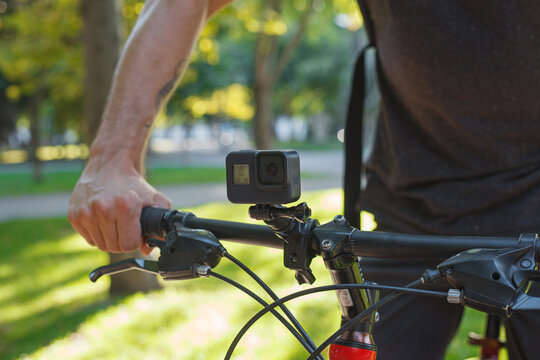 Action camera mounted on the handlebar of a bicycle that a male cyclist is holding