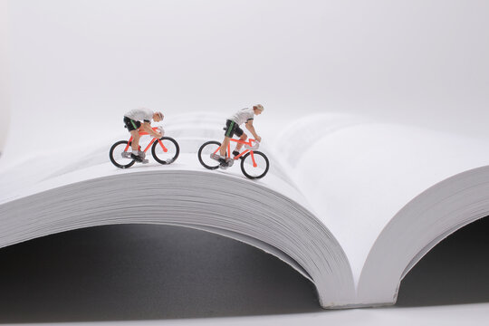 the Mini people,  Small figures cycling on open book