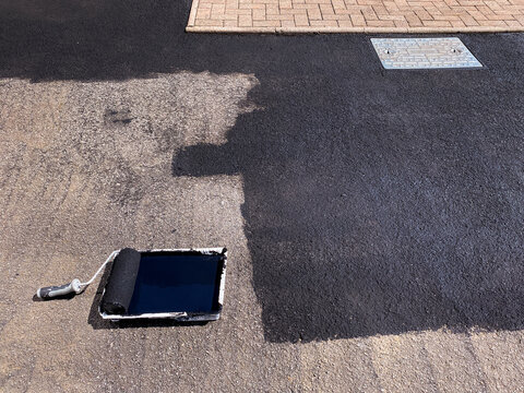 Paint roller and paint tray being used to seal a tarmac driveway with black paint