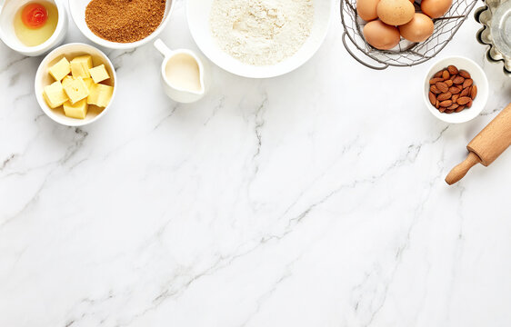 Baking background with ingredients standing on a marble table surface