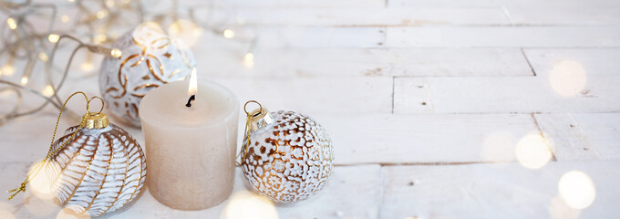 White christmas decoration with candle on vintage wood. Horizontal close-up with golden bokeh and short depth of field. Atmospheric background for christmas greetings. Space for text .