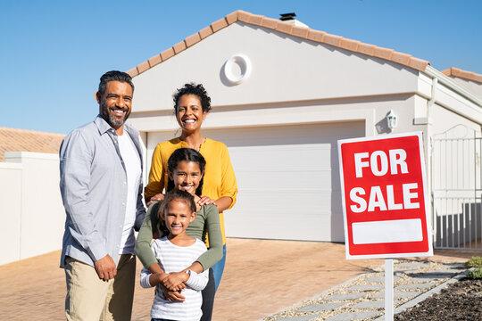 Multiethnic family standing near house sale board