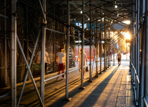 People walking down a sidewalk in New York City with the light of sunset shining through construction scaffolding overhead
