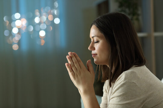 Profile of a woman praying at night at home