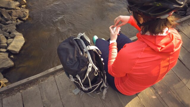 Caucasian woman sportsman in a bright sportswear helmet is resting on a bridge over the river. Cyclist with free white bags, opening the case, insert the earphone into the ear