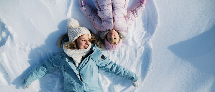 Top view portrait of cheerful mother with small daughter lying in snow in winter nature.