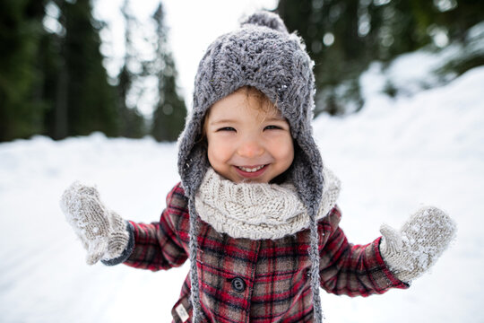 Front view portrait of cheerful small girl standing in winter nature, looking at camera.