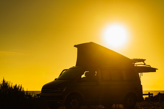 Camper van with tent on roof at sunset