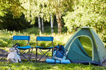 Background image of empty tent and camping gear on camping site in forest, copy space