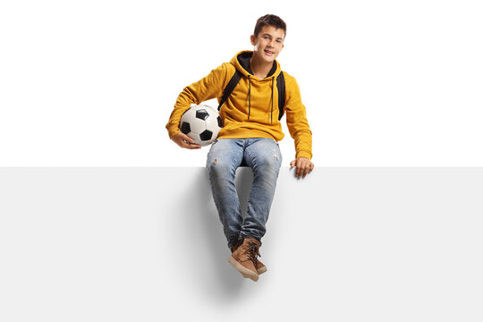 Teenager boy holding a soccer ball and sitting on a white panel board