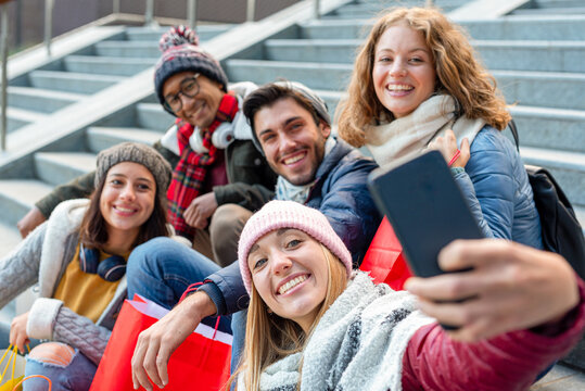 group of friends take a picture with your cell phone after shopping in the city, habits among young people addicted to social networks, group selfie, fire on the face of the blonde girl in the bottom