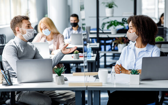 Communication and meeting in office after returning from quarantine. Young guy and african american woman in protective mask talking through glass board at workplace