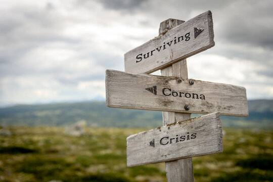 surviving corona crisis text on signpost
