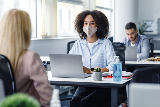 Work with client after quarantine and social distancing. Friendly african american woman in protective mask talking to european lady, sitting at workplace with laptop