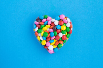 Top view of colorful candy in the shape of a heart on the blue background